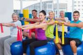 Happy people exercising with resistance bands in gym — ストック写真