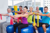 Happy people exercising with resistance bands in gym — Stok fotoğraf
