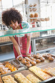 Smiling employee moving over the pastry — Stock Photo