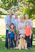 Family with dog smiling to camera — Foto de Stock
