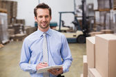 Manager holding clipboard in warehouse — Stock Photo