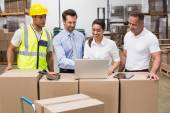 Warehouse managers and worker looking at laptop — Stok fotoğraf
