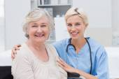 Nurse with arm around senior patient — Stock Photo
