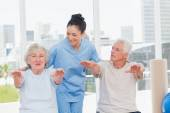 Trainer assisting senior couple to exercise — Stock Photo