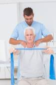 Physiotherapist assisting man in exercising — Stock Photo