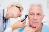 Doctor examining senior patients ear — Stock Photo
