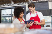 Colleagues in red apron using tablet — Stock Photo
