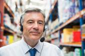 Warehouse manager giving orders on headset — Stock Photo
