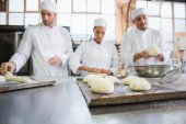 Serious colleagues kneading uncooked dough — Stock Photo