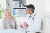 Doctor writing prescriptions for senior patient — Stock Photo