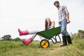 Man pushing his girlfriend in a wheelbarrow — Stock Photo