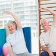 Senior couple doing stretching exercise in gym — Stock Photo #69010121