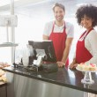 Colleagues posing behind the counter — Stock Photo #69010305