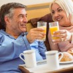 Happy mature couple having breakfast in bed — Stock Photo #69010385