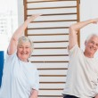Senior couple doing stretching exercise — Stock Photo #69010617