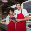 Happy co-workers in red apron holding tablet — Stock Photo #69010917
