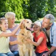 Family petting their dog in the park — Stock Photo #69012709