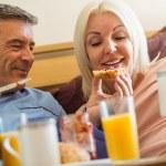 Happy mature couple having breakfast in bed — Stock Photo #69013797