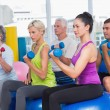 People working out with dumbbells in gym class — Stock Photo #69015883