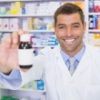 Handsome pharmacist showing medicine bottle — Stock Photo #69018167