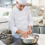 Baker cracking eggs on flour — Stock Photo #69018669