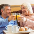 Happy mature couple having breakfast in bed — Stock Photo #69018677