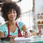 Smiling waitress writing on notepad — Stock Photo #69018687