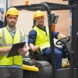 Smiling warehouse worker and forklift driver — Stock Photo #69018725
