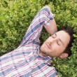 Handsome man relaxing in field — Stock Photo #69018749