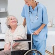 Nurse looking at patient sitting on wheelchair — Stock Photo #69019183