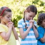 Children saying their prayers in park — Stock Photo #69019801