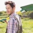 Happy farmer carrying his shovel — Stock Photo #69019955
