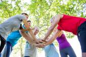 Happy athletic group putting their hands together  — Stock Photo