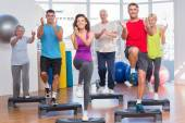 People performing step aerobics exercise in gym — Stock Photo