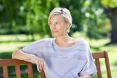 Smiling blonde sitting on a bench  — Stock Photo