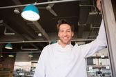Smiling baker standing at bakery — Stock Photo