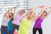 Women practicing stretching exercise at fitness studio — Stock Photo
