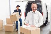 Manager achter stapel van kartonnen dozen — Stockfoto