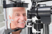 Senior patient using slit lamp at clinic — Stock Photo