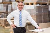 Smiling boss leaning on stack of cartons — Stock Photo