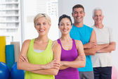 Fit people standing arms crossed at gym — Stock Photo