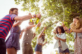 Happy hipsters spraying beer bottles — Stock Photo