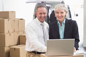 Colleague with laptop at warehouse — Stock Photo