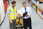 Warehouse worker talking with his manager — Stock Photo