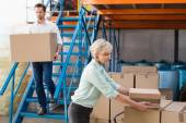 Warehouse managers loading a trolley — Stock Photo