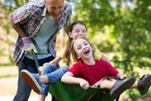Father and his children playing with wheelbarrow — Stockfoto
