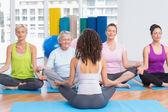 Люди, практикующие позе лотоса в класс йоги — Стоковое фото
