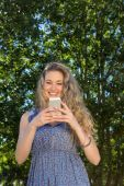 Pretty blonde using phone in the park — Stock Photo
