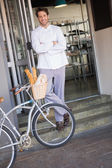 Baker with arms crossed and bike — Stock Photo