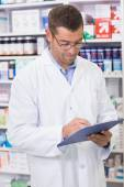 Focused pharmacist writing on clipboard — Zdjęcie stockowe